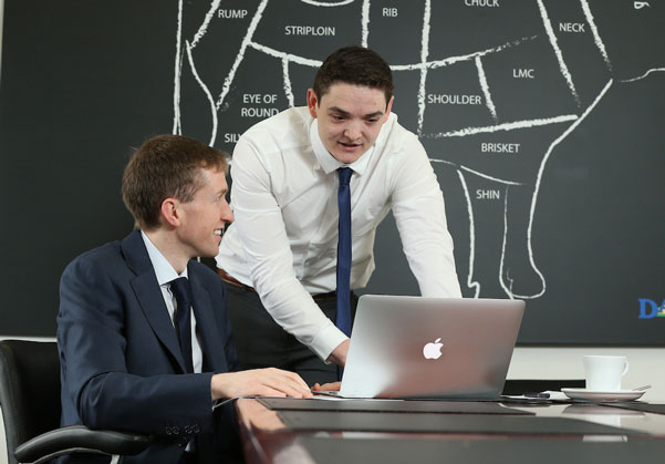 Two men in suits looking at a laptop